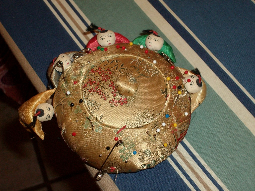 pin cushion with decorative guy falling off