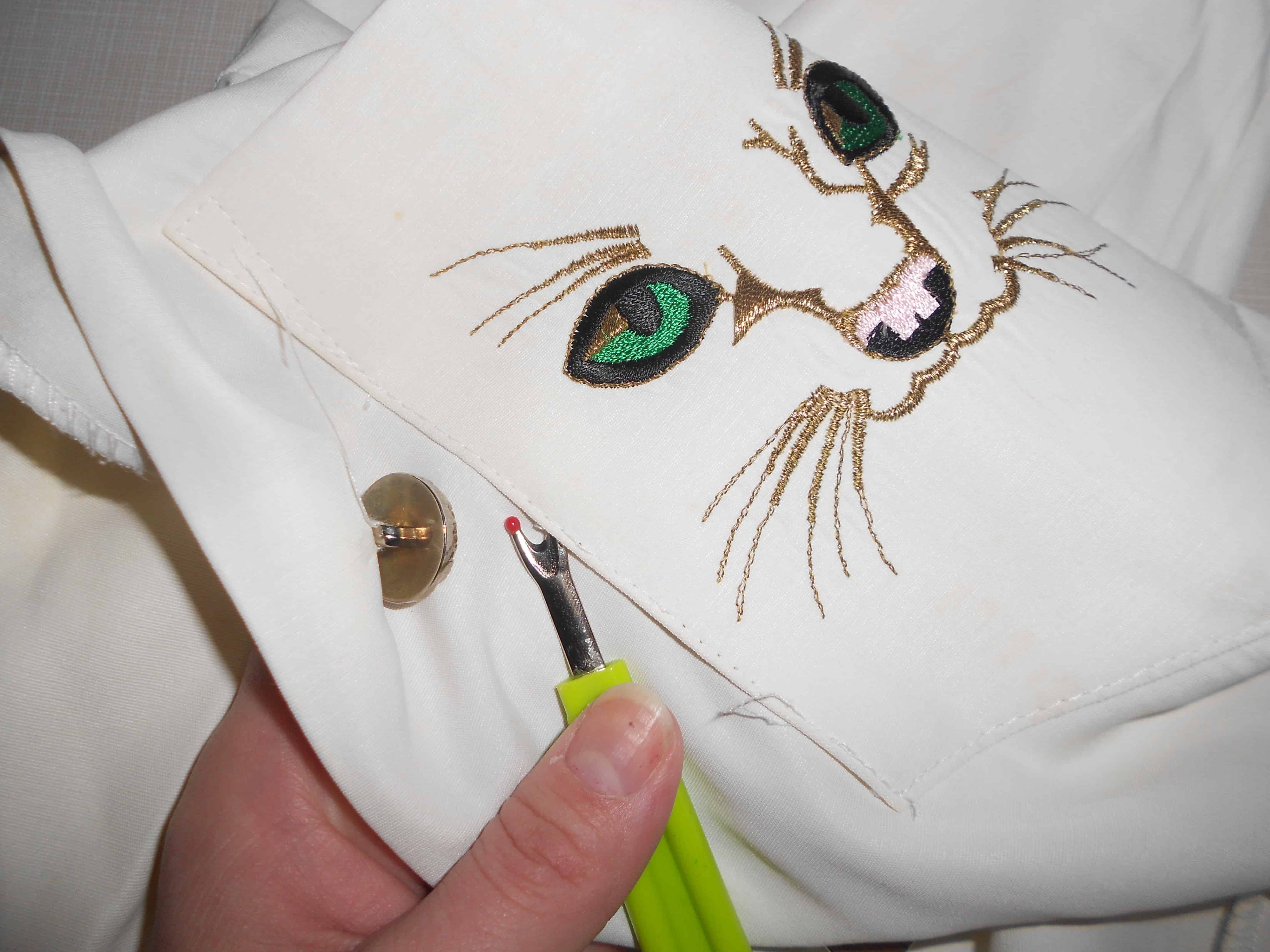 using seam ripper to remove cat pocket from shirt
