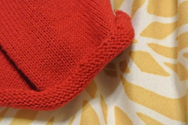curled raw edge of sweater sleeve