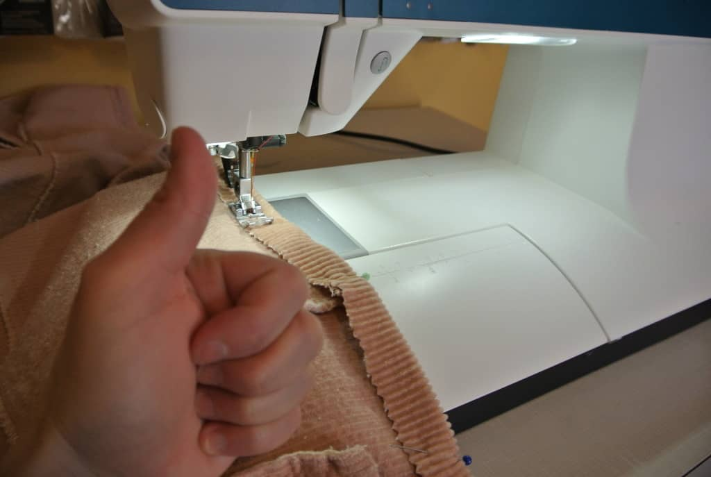 giving thumbs up in front of sewing machine