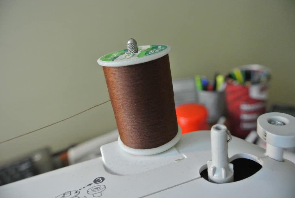 spool of brown thread on sewing machine