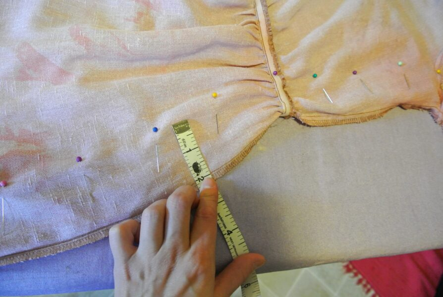 measuring and pinning sides of dress