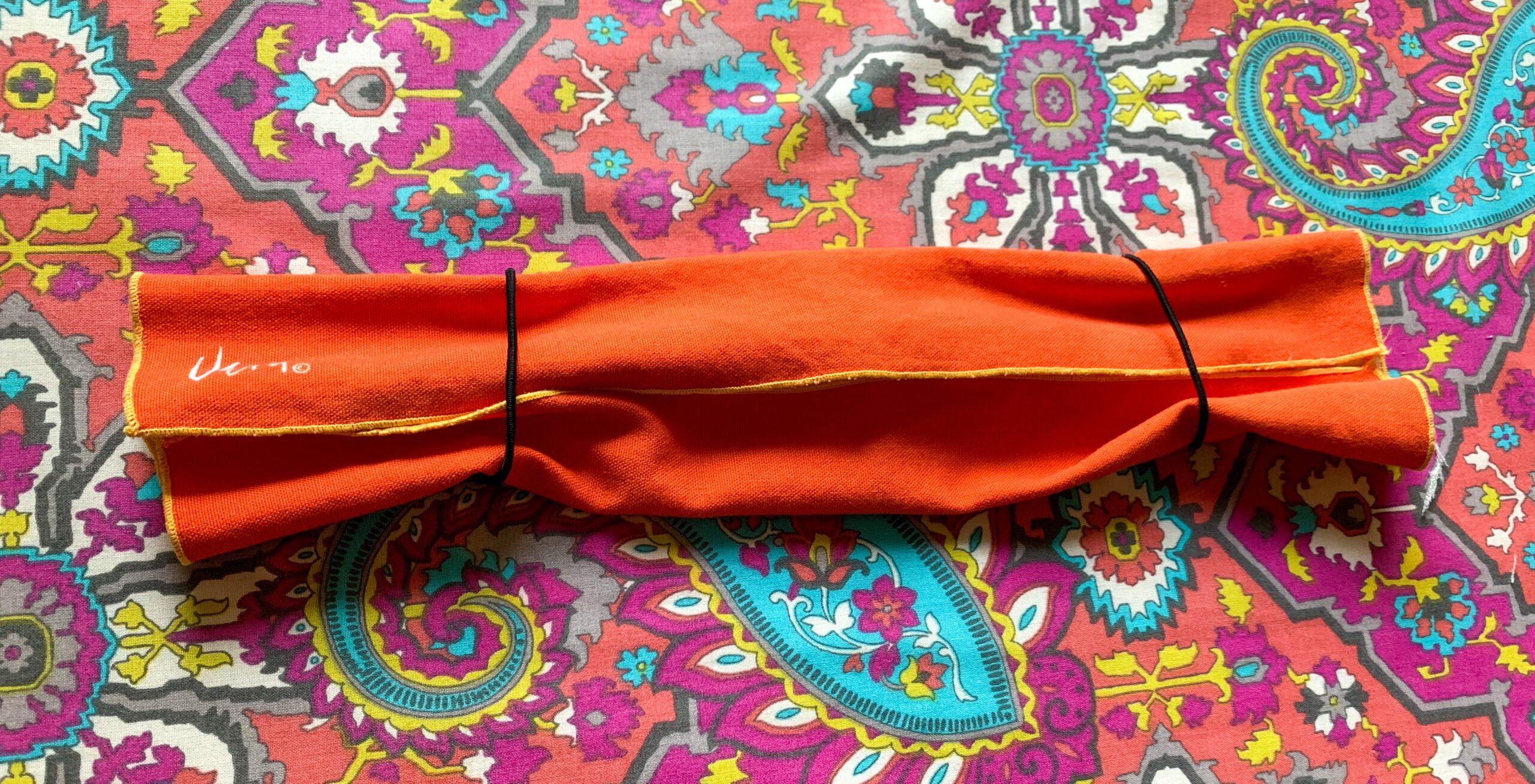 threading hair ties through cloth napkin for diy face mask