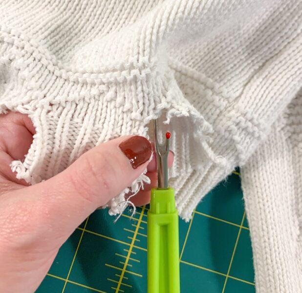 using seam ripper to distress sweater