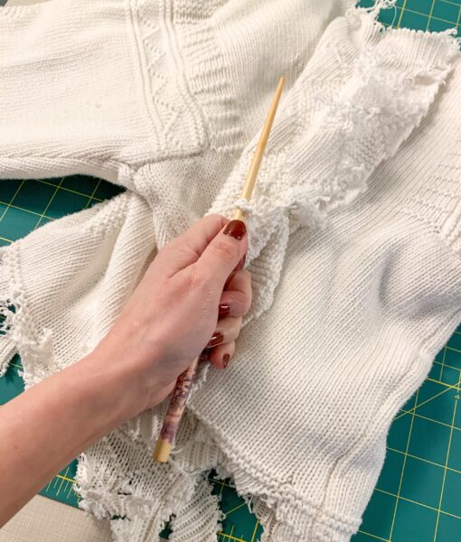 using chopstick to unravel sweater