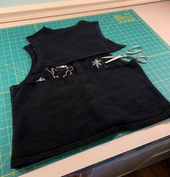 cutting across back of sweater vest