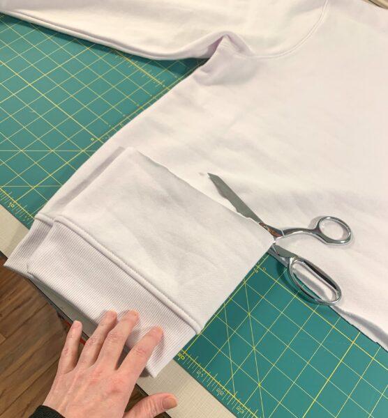 folding bottom of sweatshirt over while cutting