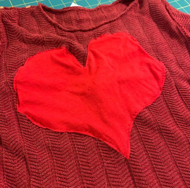 heart sewn onto sweater