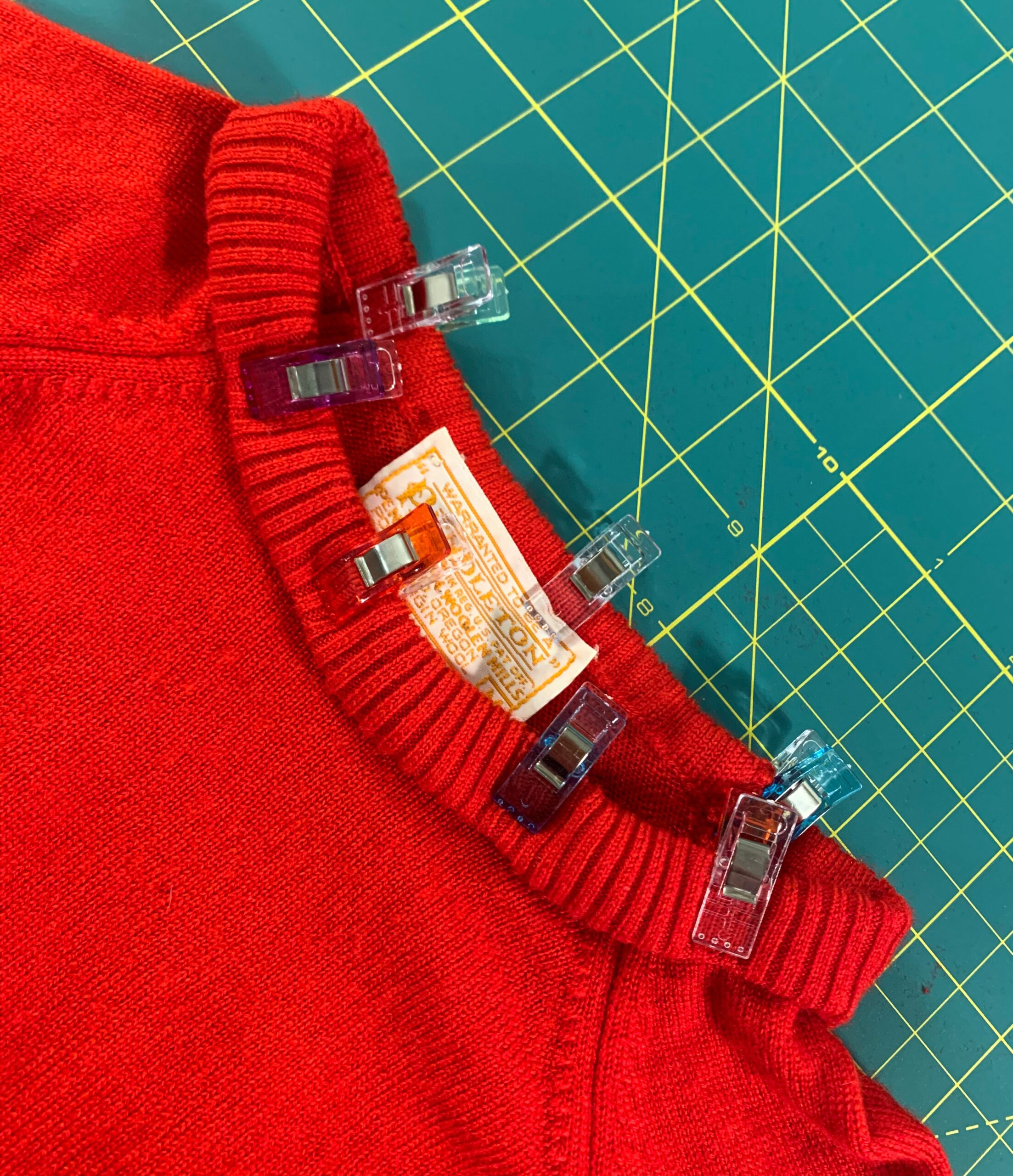 sewing clips holding down new neckline of sweater