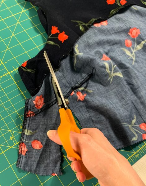 cutting off extra fabric from side of top