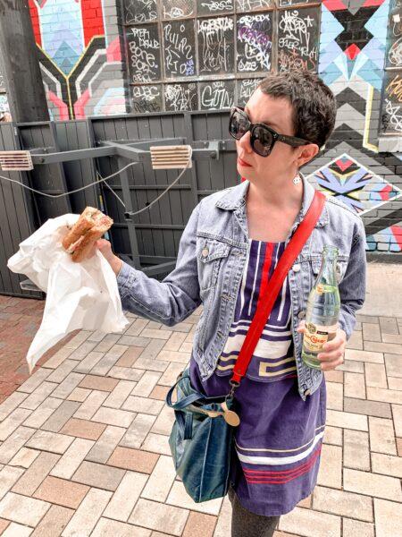jillian in denim jacket holding sandwich